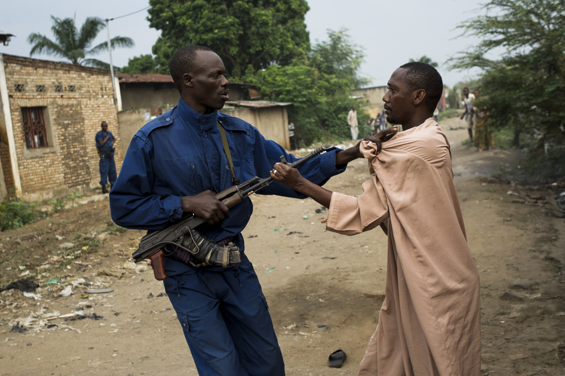 A policeman jostles with a resident of the largely opposition neighbourhood of Cibitoke in Bujumbura, Burundi, on June 27, 2015. Police conducted a raid on the neighbourhood this morning, searching for weapons and arresting a man they accused of being a leader of an opposition party, who they claim was hiding weapons.