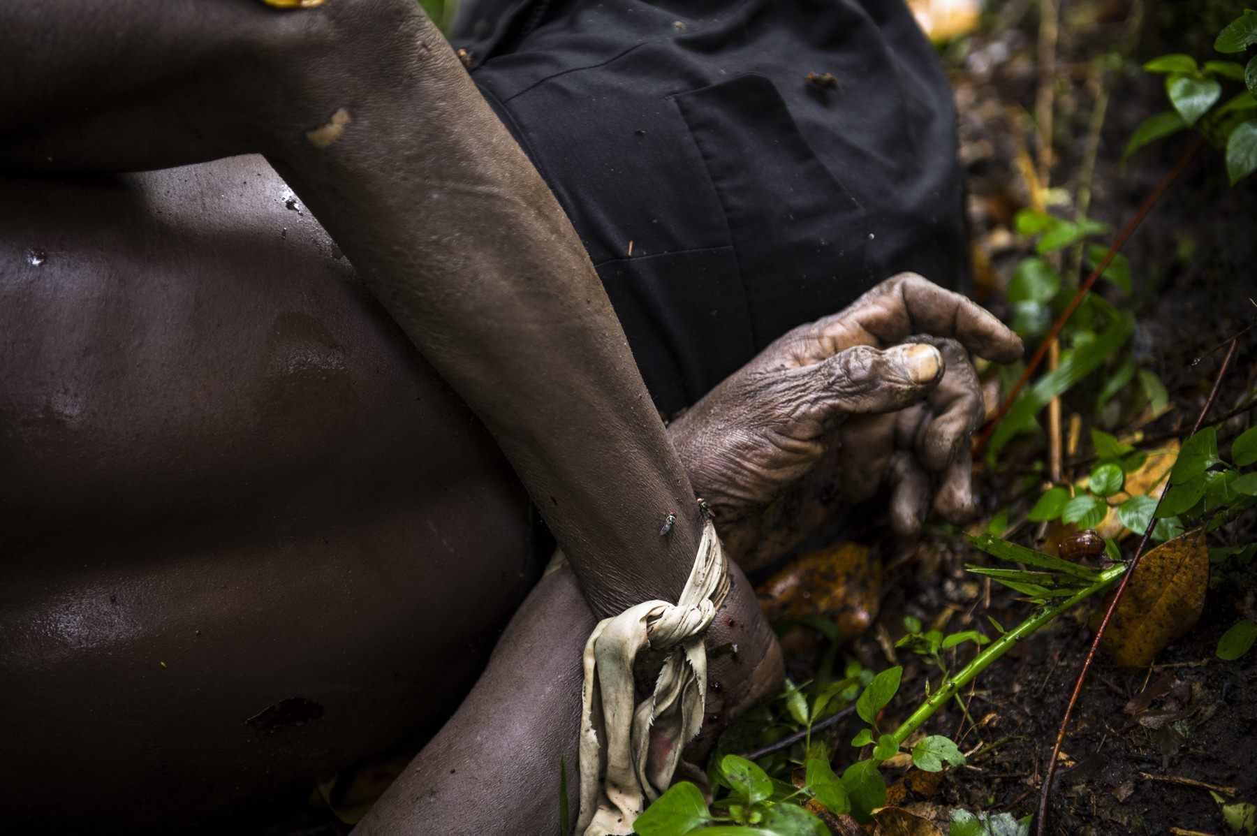 "The bodies of two men killed near the village of Mabenga in the Democratic Republic of the Congo's restive North Kivu province, lie with their hands tied behind their backs in the jungle beside the Rwindi river on July 29, 2012. M23 rebels accuse the Congolese army of massacring up to 70 people here, throwing their bodies into the river. M23 claim that the army accused those killed of having a ""familiar relationship"" with the rebel group."
